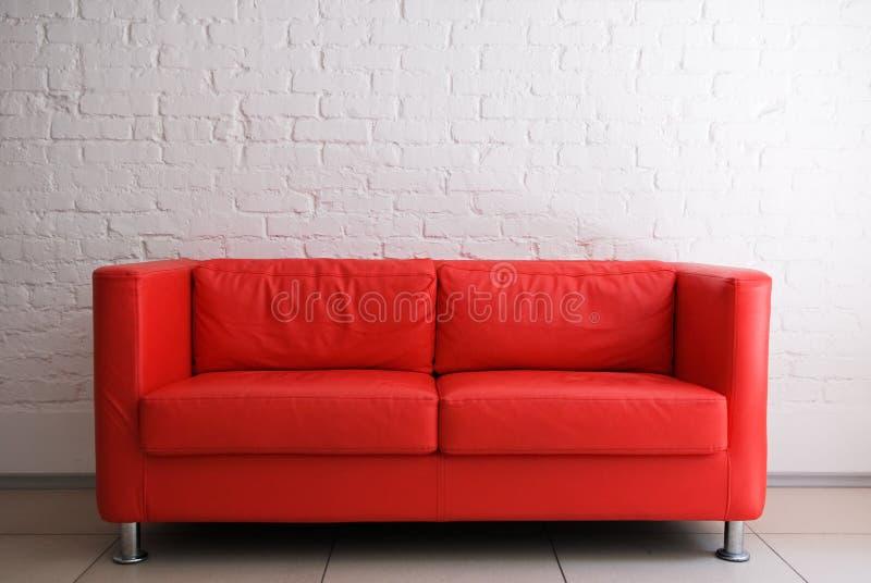 Rotes Sofa und Backsteinmauer stockbilder