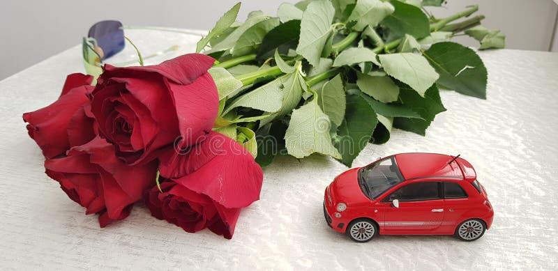 Rotes Spielzeug Fiats 500 auf weißer Tabelle nahe dem Blumenstrauß mit fünf Rosen lizenzfreies stockfoto