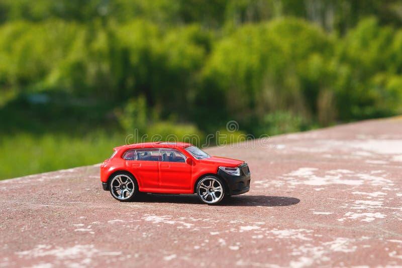 Rotes Spielzeugauto auf dem Hintergrund von grünen Bäumen, gibt es ein Auto auf einer Betonplatte in der Tageszeit ein hellen Son lizenzfreie stockfotografie
