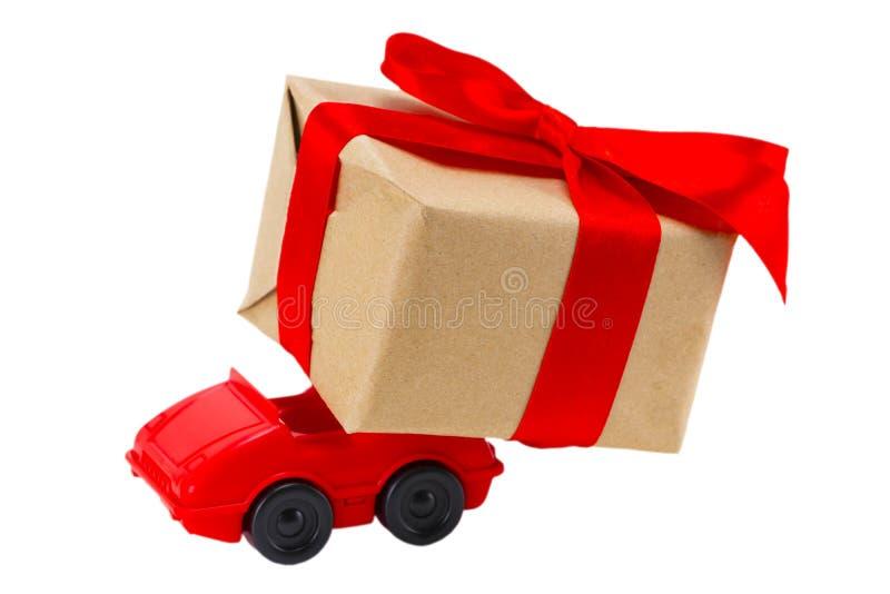 Rotes Spielzeugauto, das Geschenkkasten auf einem weißen Hintergrund liefert lizenzfreie stockfotos