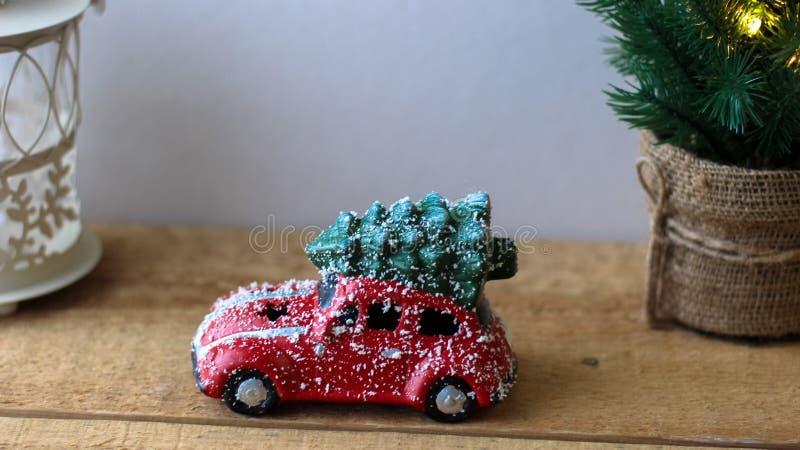 Rotes Spielzeugauto tragender Weihnachtsbaum auf dem Dach stockfotografie