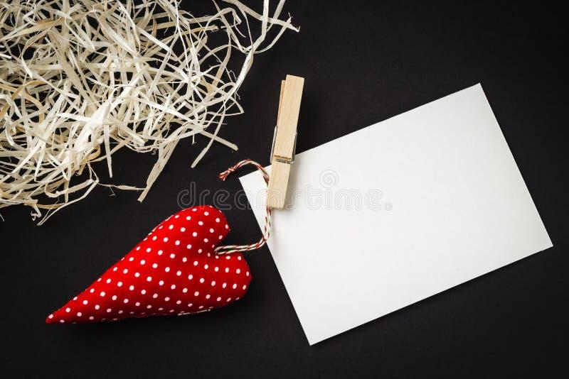 Rotes Spielzeugherz und leere Karte auf Schwarzem lizenzfreies stockfoto