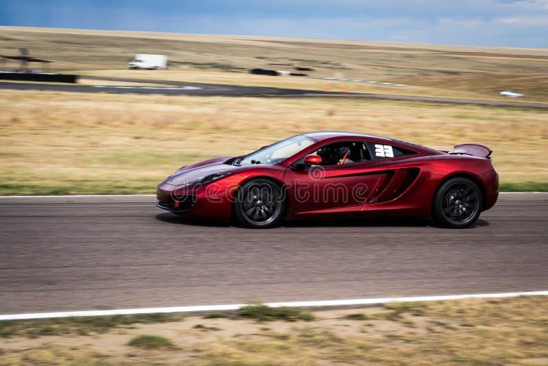 Rotes Sportauto auf Rennstrecke lizenzfreie stockbilder