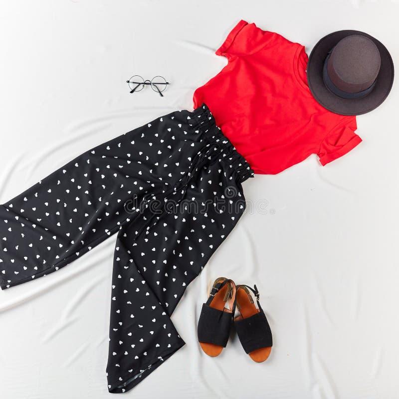 Rotes stilvolles T-Shirt, schwarze Hosen, Sandalen, Gläser auf weißem Hintergrund stockfotos