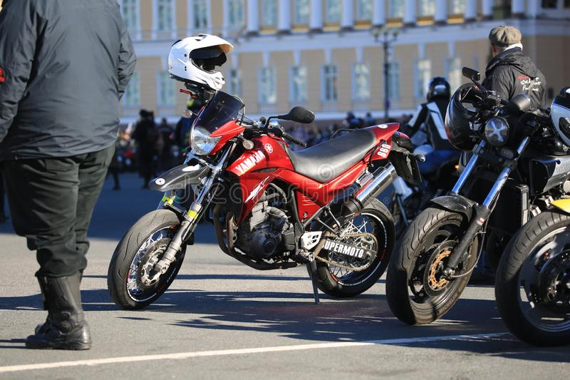 Rotes supermoto Fahrrad Yamaha XT660X unter anderen Fahrrädern und Leuten stockbilder