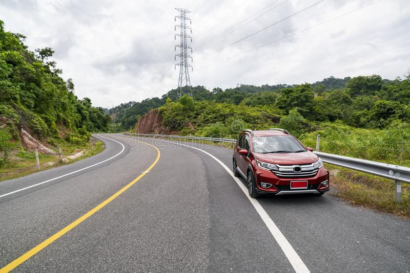 Rotes Suv-Auto auf Asphaltstraße mit dem Gebirgsgrün-Waldtransport, zu reisen Konzept lizenzfreie stockfotos