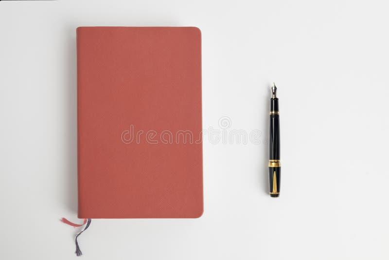 Rotes Tagebuch und Füllfederhalter stockbilder