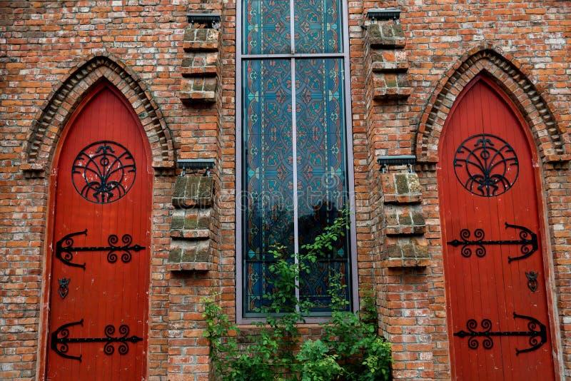 Rotes Tor und buntes Glasfenster lizenzfreie stockfotografie