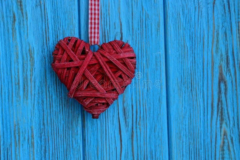 Rotes umsponnenes Herz, das an einer blauen hölzernen Wand hängt lizenzfreie stockfotografie