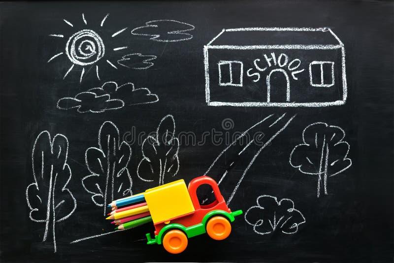 Rotes und gelbes Spielzeugauto transportiert bunte Bleistifte zum Schulhaus stockbilder