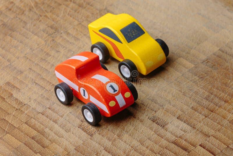 Rotes und gelbes Weinlesespielzeugauto auf einer Holzoberfläche stockfoto