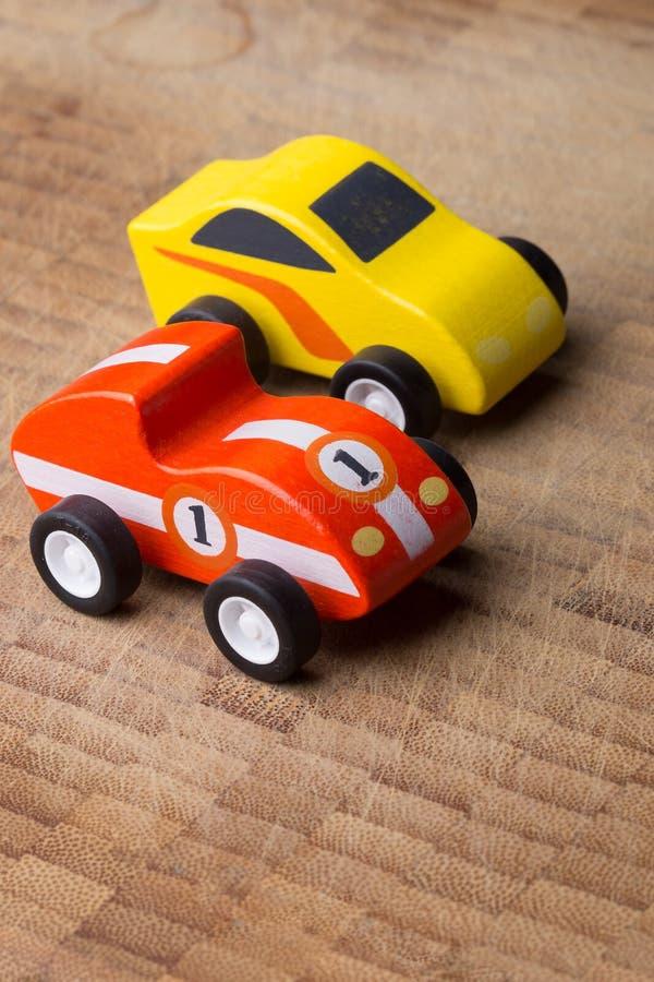 Rotes und gelbes Weinlesespielzeugauto auf einer Holzoberfläche lizenzfreies stockbild