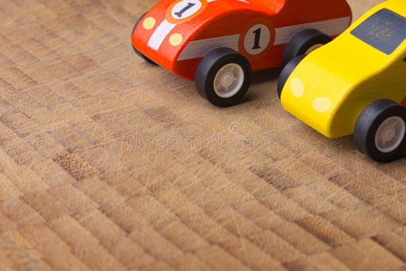 Rotes und gelbes Weinlesespielzeugauto auf einer Holzoberfläche lizenzfreie stockfotos