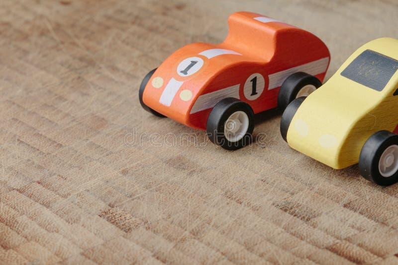 Rotes und gelbes Weinlesespielzeugauto auf einer Holzoberfläche stockbild