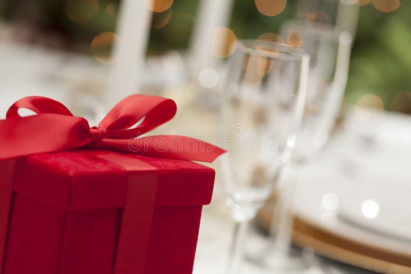 Rotes Weihnachtsgeschenk mit Gedeck bei Tisch lizenzfreies stockbild