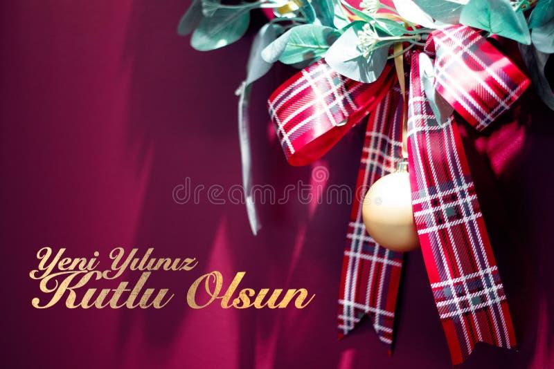 Rotes Weihnachtsgeschenkband auf rotem Hintergrund mit Text Yeni-yiliniz kutlu olsun Durchschnittguten rutsch ins neue jahr stockfotografie