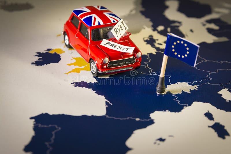 Rotes Weinleseauto mit Union Jack-Flaggen- und -brexit- oder -tschüsswörtern über einer UE-Karte und -flagge lizenzfreie stockfotos