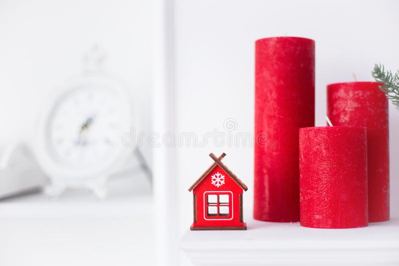 Rotes Winterhaus des Spielzeugs im festlichen Hauptinnenraum mit Weihnachtskerzen und weißer Wand auf Hintergrund lizenzfreie stockfotografie
