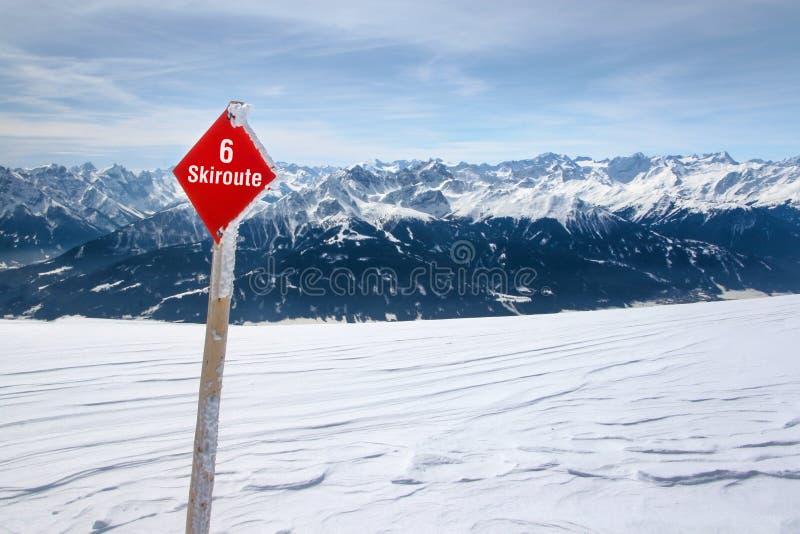 Rotes Zeichen des Skiweges 6 auf frischem Schnee mit österreichischen Alpen lizenzfreies stockbild