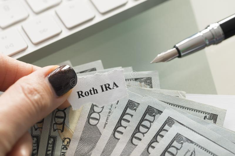 Roth IRA, μεμονωμένος απολογισμός αποχώρησης, σχέδιο με τα αμερικανικά δολάρια μετρητών σε έναν πίνακα στοκ εικόνα