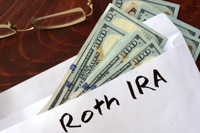 Roth IRA escrito en un sobre con los dólares fotografía de archivo