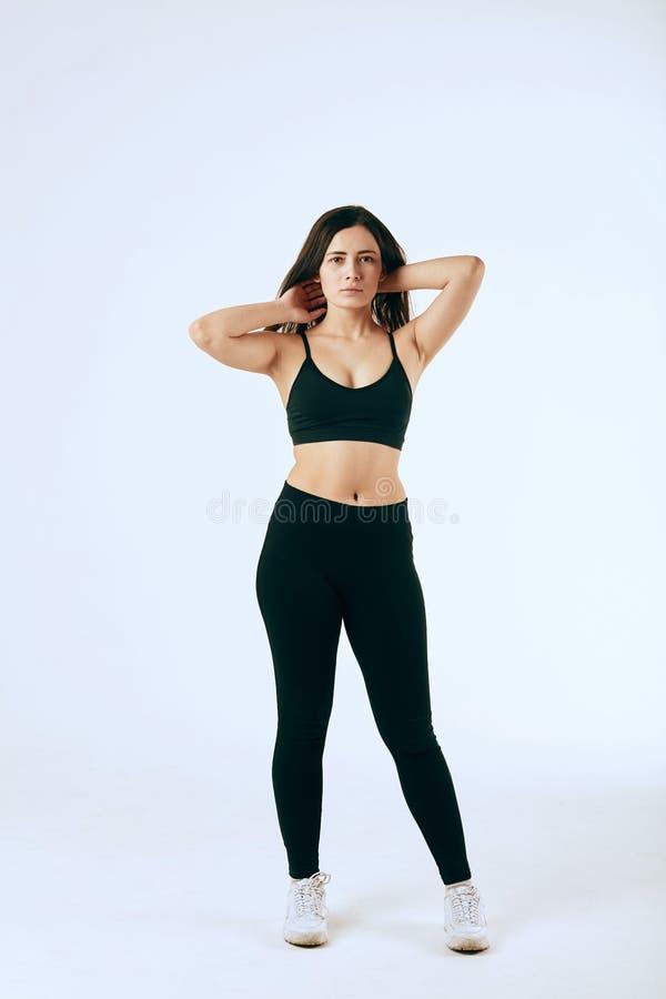 Rothaarige Frau in der schwarzen Sportkleidung, die auf weißem Hintergrund aufwirft stockfotos
