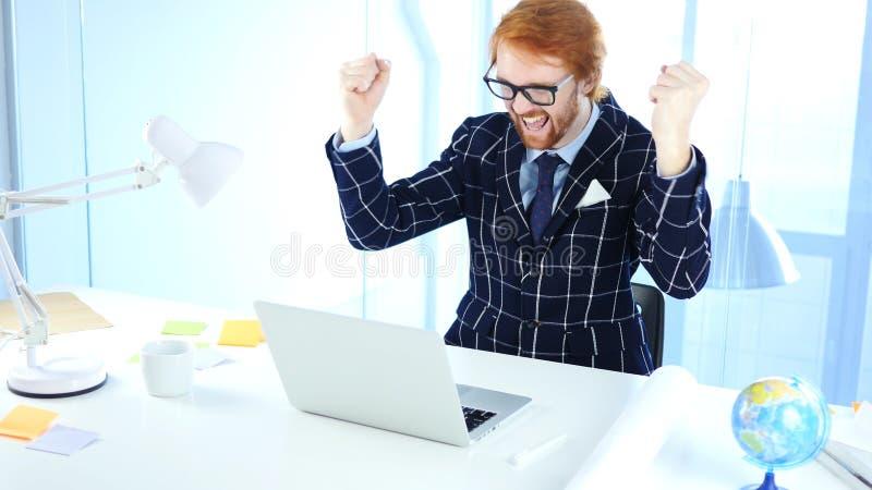 Rothaarige-Geschäftsmann Celebrating Success beim Arbeiten an Laptop, Aufregung lizenzfreie stockfotos