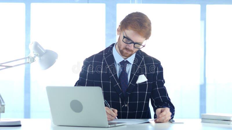 Rothaarige-Geschäftsmann Writing im Büro, Dokumentation stockfotos