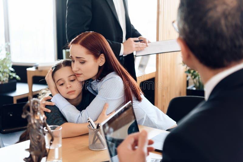 Rothaarige traurige Frau umarmt wenig störte das Mädchen, das in Rechtsanwalt ` s Büro für Scheidung sitzt stockbilder