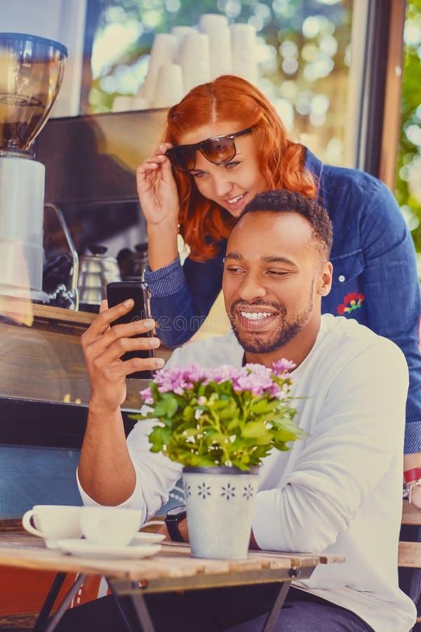 Rothaarige weiblich und schwarzes Lächeln männlich unter Verwendung des Smartphone lizenzfreie stockfotos