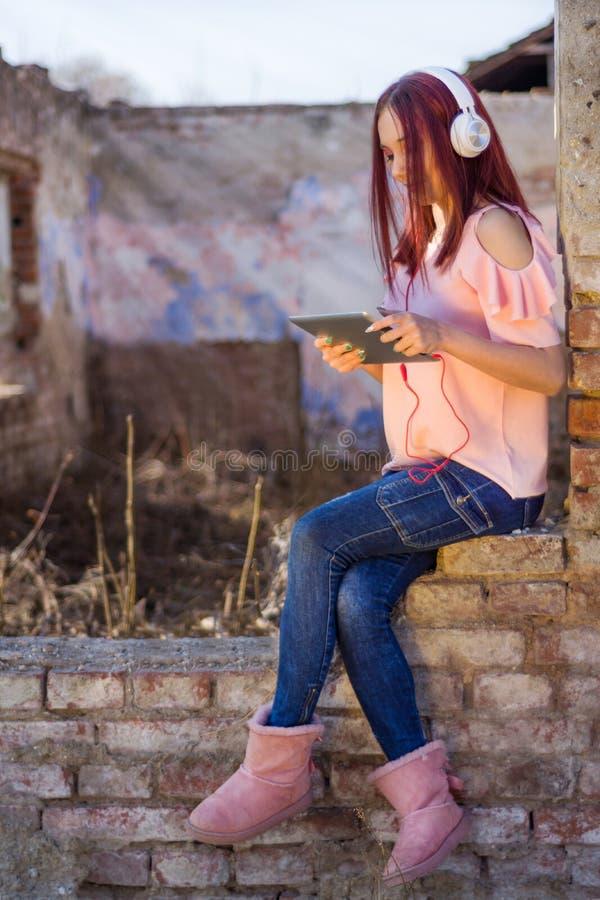 Rothaarigedame mit digitaler Tablette hörend Musik auf Kopfhörern auf Ruinenwandziegelsteinen des Retro- Hauses im Sonnenuntergan lizenzfreie stockfotografie