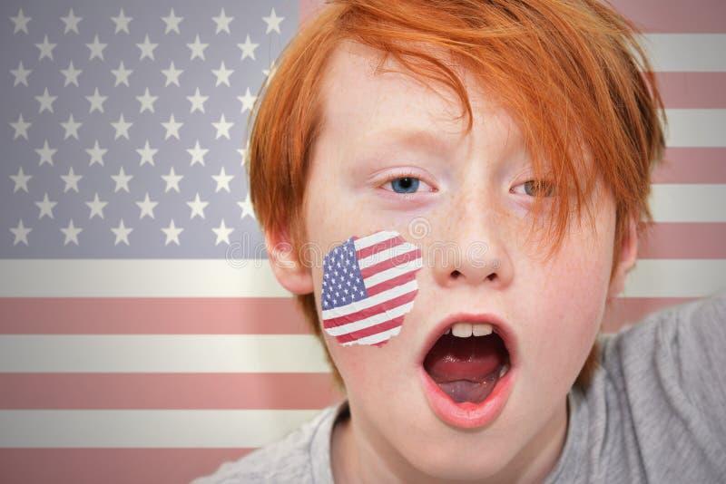 Rothaarigefanjunge mit der amerikanischen Flagge gemalt auf seinem Gesicht stockbild