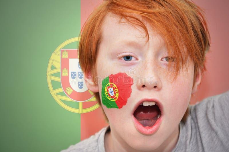 Rothaarigefanjunge mit der portugiesischen Flagge gemalt auf seinem Gesicht stockfotos