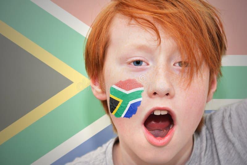 Rothaarigefanjunge mit Südafrika-Flagge gemalt auf seinem Gesicht stockbilder