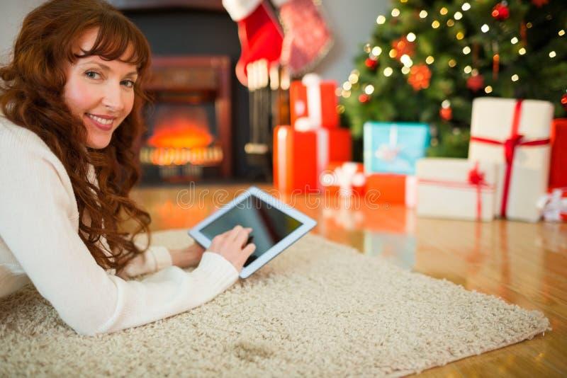 Rothaarigefrau, die auf Boden unter Verwendung der Tablette am Weihnachten liegt stockfotografie