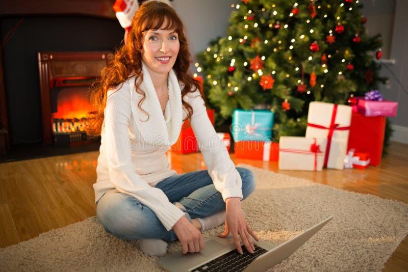 Rothaarigefrau, die auf Boden unter Verwendung des Laptops am Weihnachten sitzt lizenzfreies stockbild