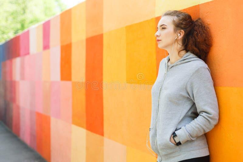 Rothaarigefrau, die auf heller Wand sich lehnt stockfoto