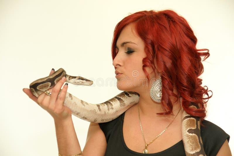 Rothaarigefrau, die eine Schlange küsst stockfoto