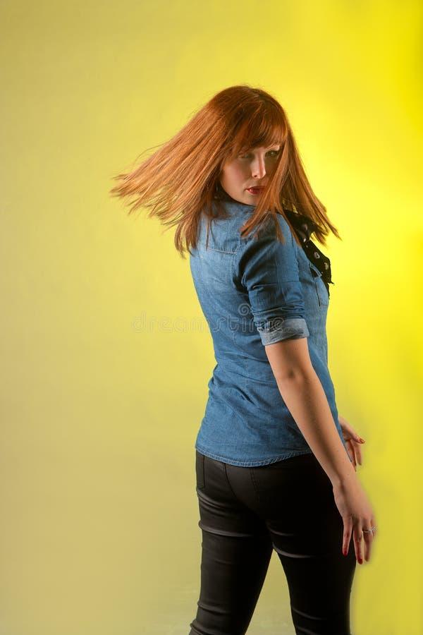 Rothaarigefrau, die gelben Hintergrund schaut stockfotografie