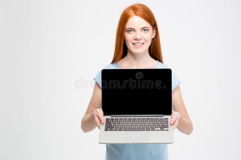 Rothaarigefrau, die leeren Laptop-Computer Schirm zeigt stockbild