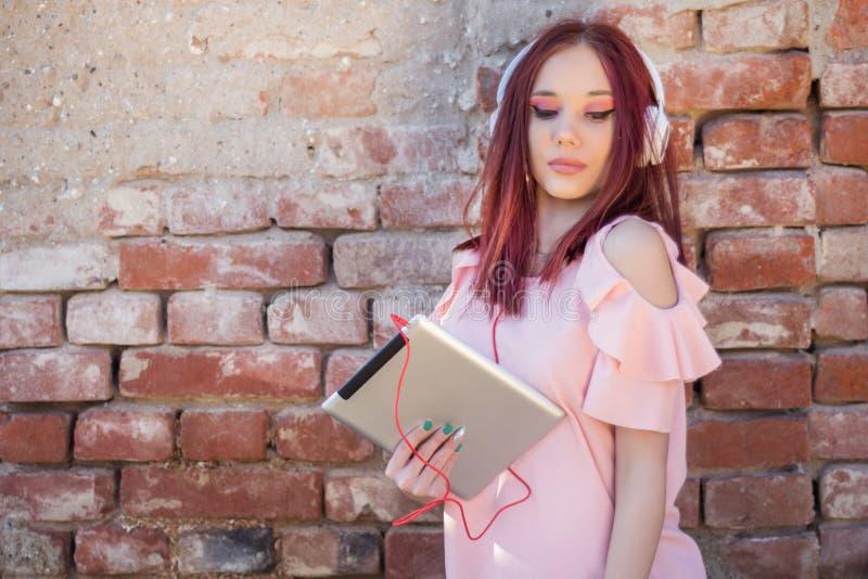Rothaarigefrau, die Musik auf digitaler Tablette mit Kopfhörern gegen die Backsteinmauer im Freien hört lizenzfreie stockfotos