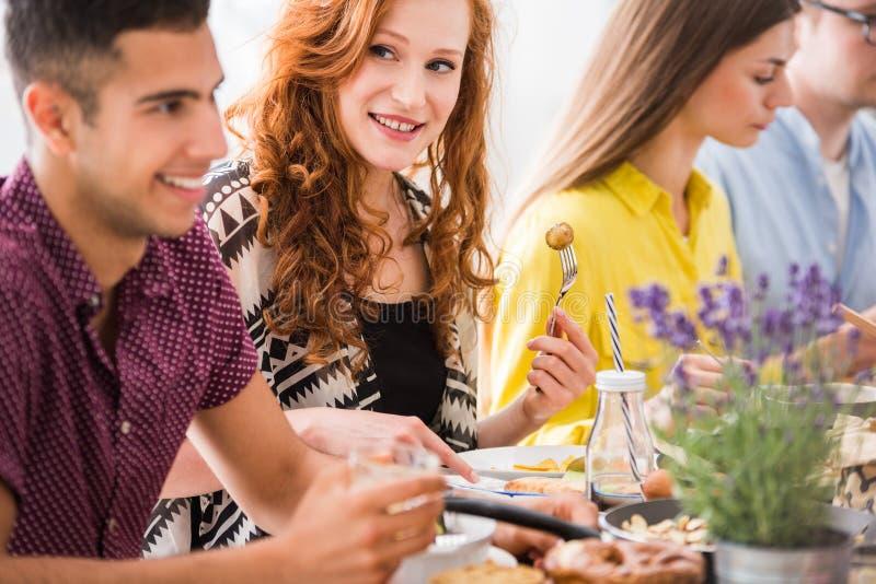 Rothaarigefrau, die vegetarisches Abendessen genießt stockbilder