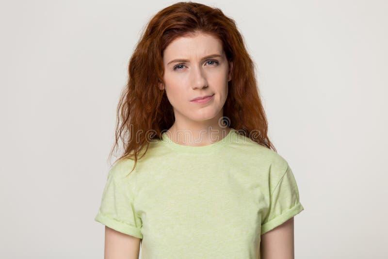 Rothaarigefrau glaubt verwirrter misstrauischer Haltung über grauem Studiohintergrund stockfotografie