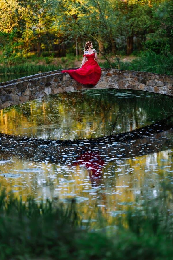 Rothaarigefrau im roten Kleid, das auf Steinbrücke sitzt lizenzfreie stockfotografie