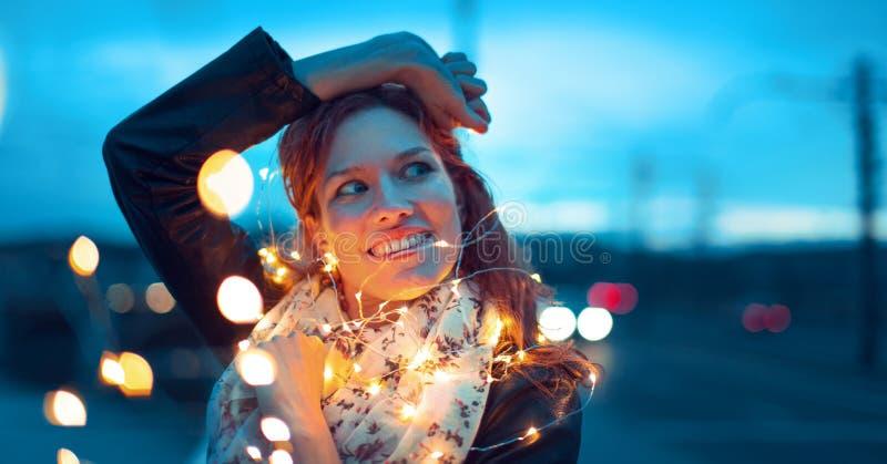 Rothaarigefrau mit den feenhaften Lichtern der Girlande, die weg schauen stockfotos