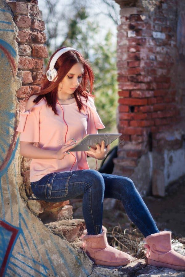 Rothaarigefrau mit digitaler Tablette hörend Musik auf Kopfhörern auf Ruinenwandroten backsteinen des Retro- Hauses lizenzfreies stockfoto