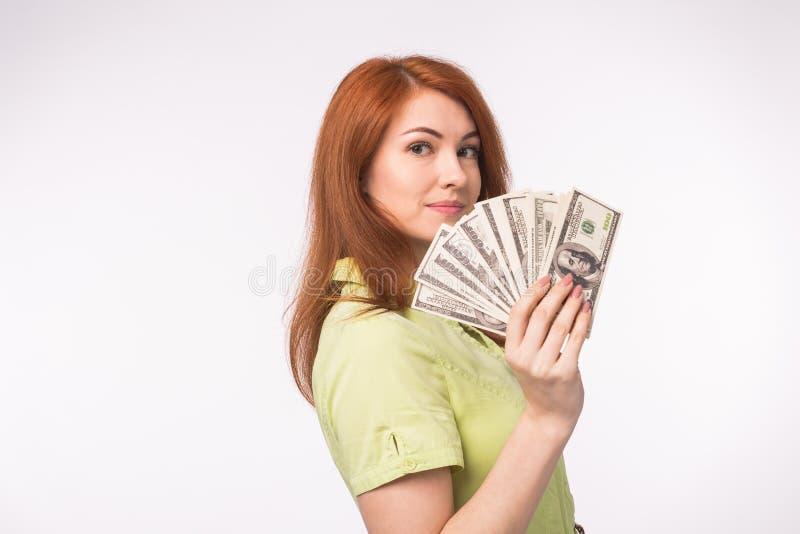Rothaarigefrau mit Geld auf weißem Hintergrund stockbild