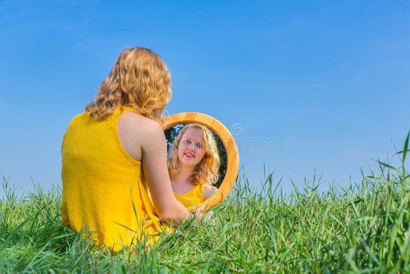 Rothaarigefrau sitzt, Spiegel draußen betrachtend stockfotos