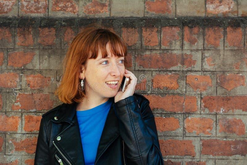 Rothaarigefrauenfrau, die an ihrem Handy spricht stockfotos