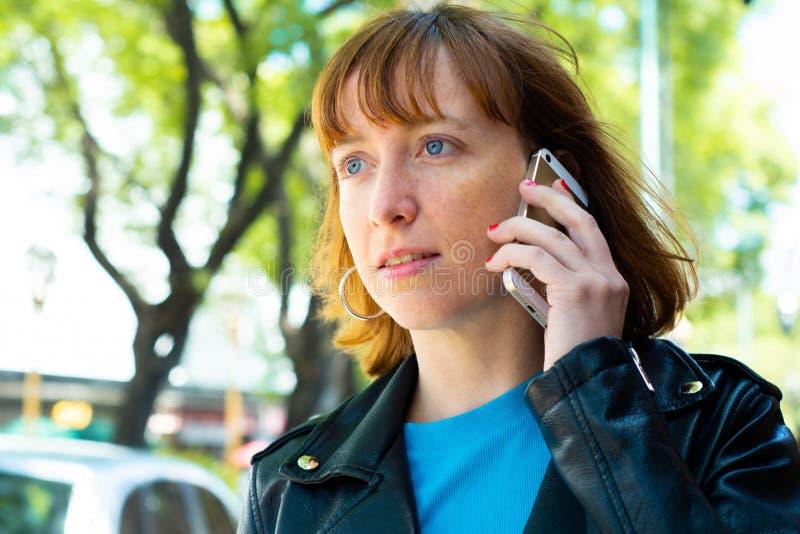 Rothaarigefrauenfrau, die an ihrem Handy spricht lizenzfreies stockfoto